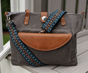 Adjustable length, woven bag strap with bright blue, orange and black Southwestern style pattern and silver clasp, attached to grey Carry All Tote Trio.