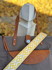 A yellow, tan and white woven bag strap displayed across a grey canvas tote with brown vegan leather accents, set on a white fence post with fall leaves behind.