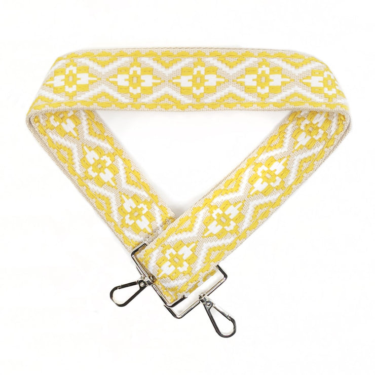 A close-up on white background of an adjustable length, woven bag strap with yellow, tan and white diamond pattern and silver clasp.