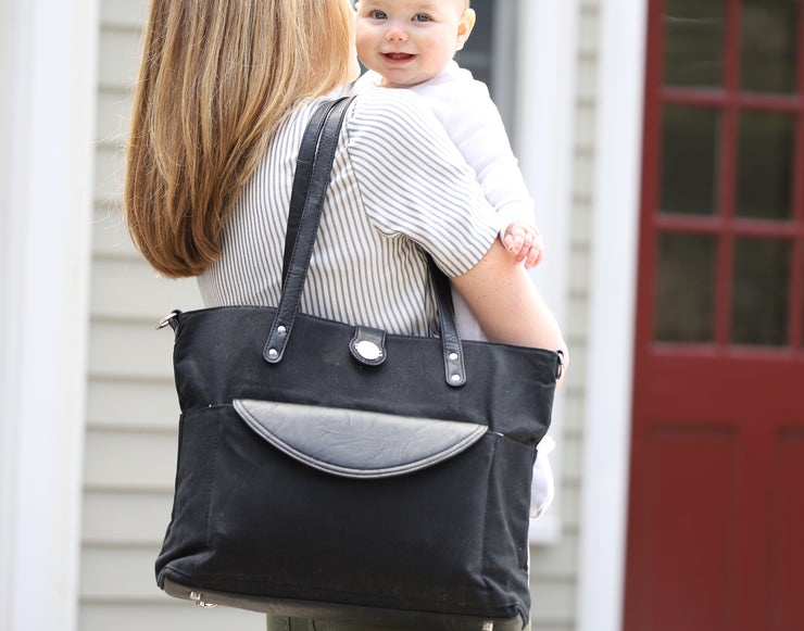 Black Carry All Tote Trio with vegan diaper clutch in front pocket worn as shoulder tote of mom carrying baby.