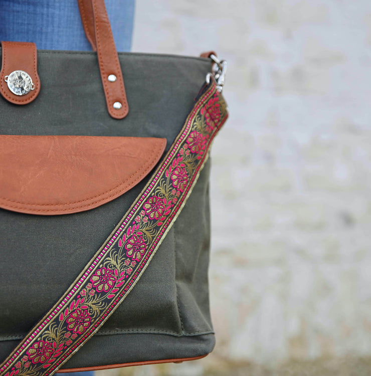 A pink, gold & black floral embroidered bag strap laying across a Forest Green waxed canvas tote with brown vegan leather accents, on a backdrop of denim and white brick.