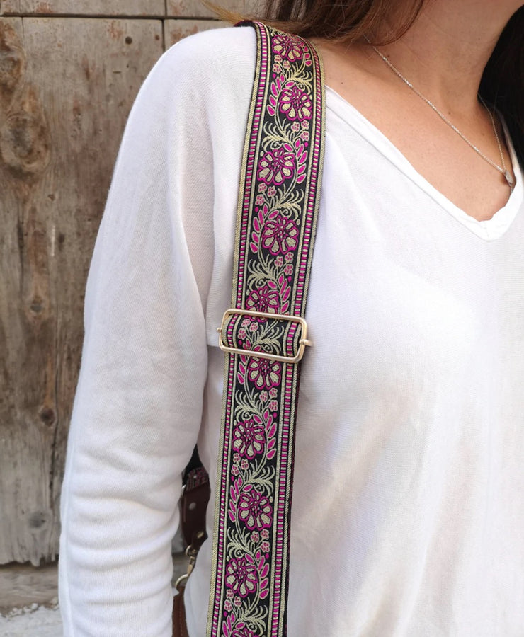 A close-up of a woman in a long sleeve white v-neck shirt wearing an adjustable length, embroidered bag strap with gold, magenta and black floral pattern and silver clasp.