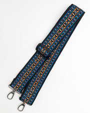 A close-up on white background of an adjustable length, woven bag strap with blue, orange and black pattern and silver clasp.