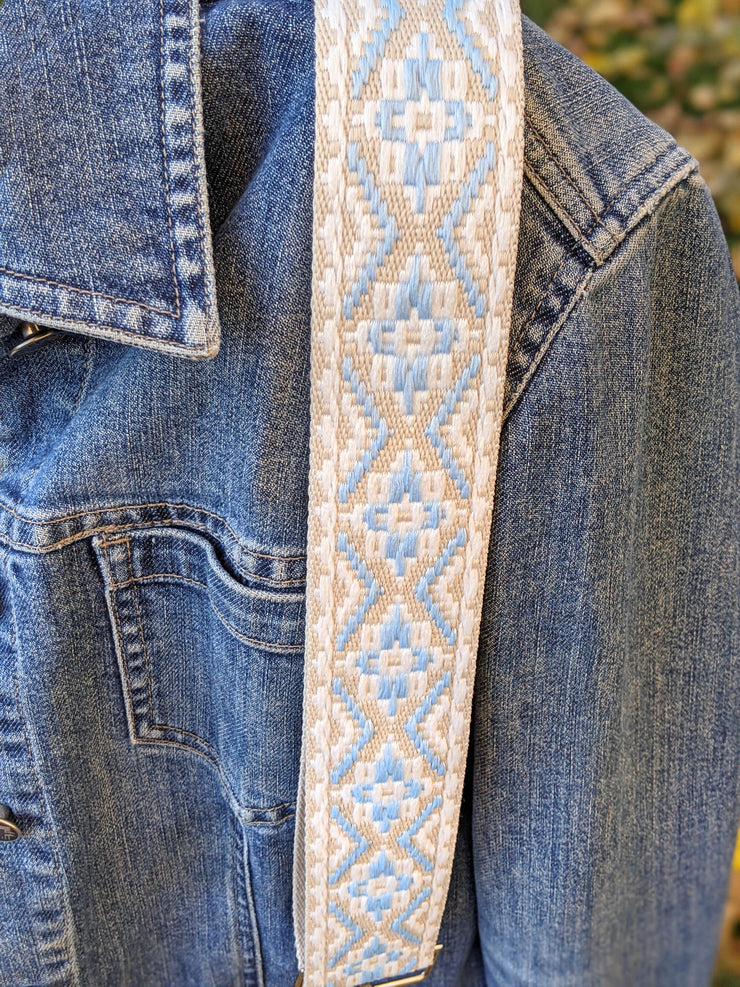 A close-up of a light blue, tan and white patterned woven bag strap worn over the shoulder of a denim jacket.