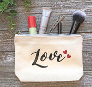 An ivory, rectangular canvas zipper case with the word LOVE printed with two red hearts, filled with make-up items and laying on a wood background.