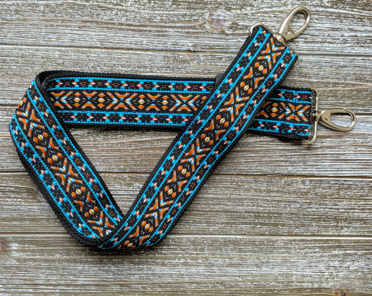 Adjustable length, woven bag strap with bright blue, orange and black southwestern style pattern and silver clasp.