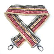 Close-up on white background of an adjustable length, woven bag strap with cream, red and green pattern with fringe on one side, and silver clasp.