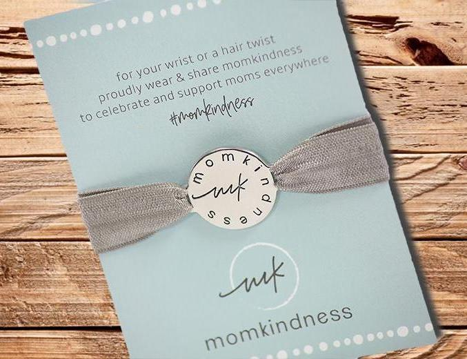 A stretchy grey hair tie with an engraved silver color charm; perfect as a gift or baby shower favor.