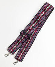 A close-up on white background of an adjustable length, woven bag strap with red, black, blue and cream striped pattern and silver clasp.