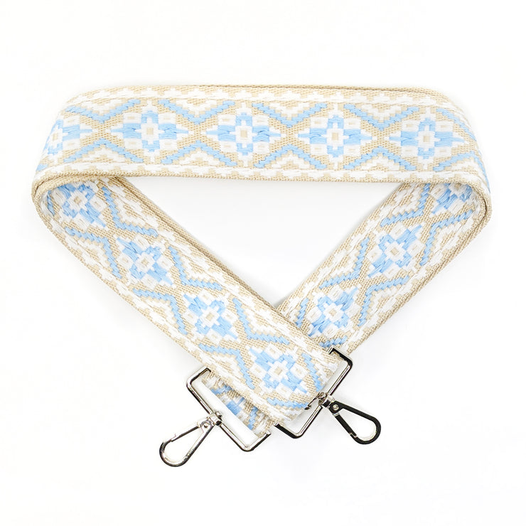A close-up on white background of an adjustable length, woven bag strap with light blue, tan and white diamond pattern and silver clasp.