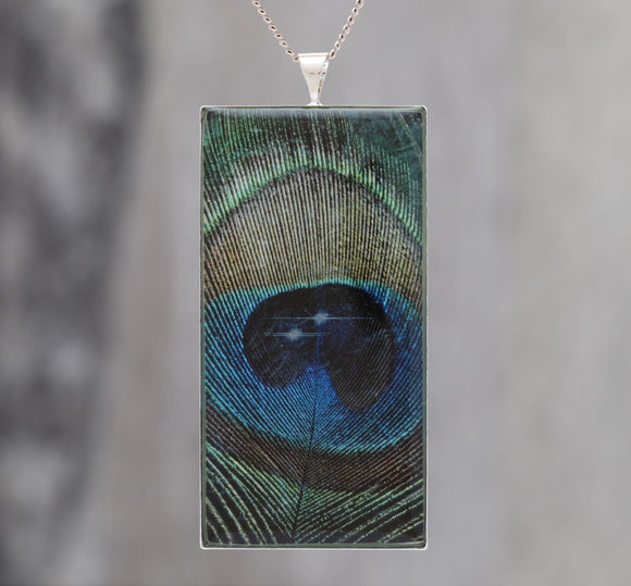 Feathers in Space  - Glow-in-the-dark pendant with a beautiful Peacock feather and star pattern