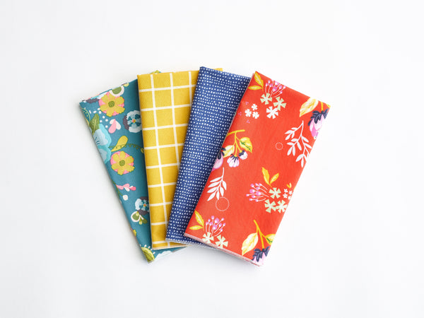 Four cloth napkins in green, yellow, blue and red