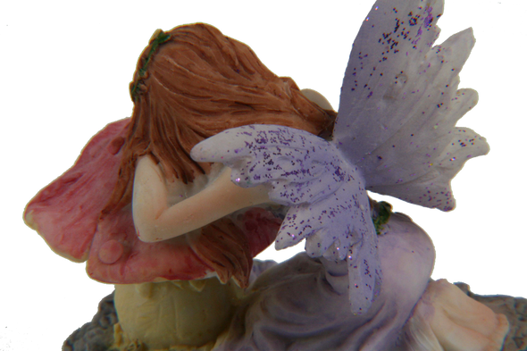 purple and pink miniature fairy on mushroom