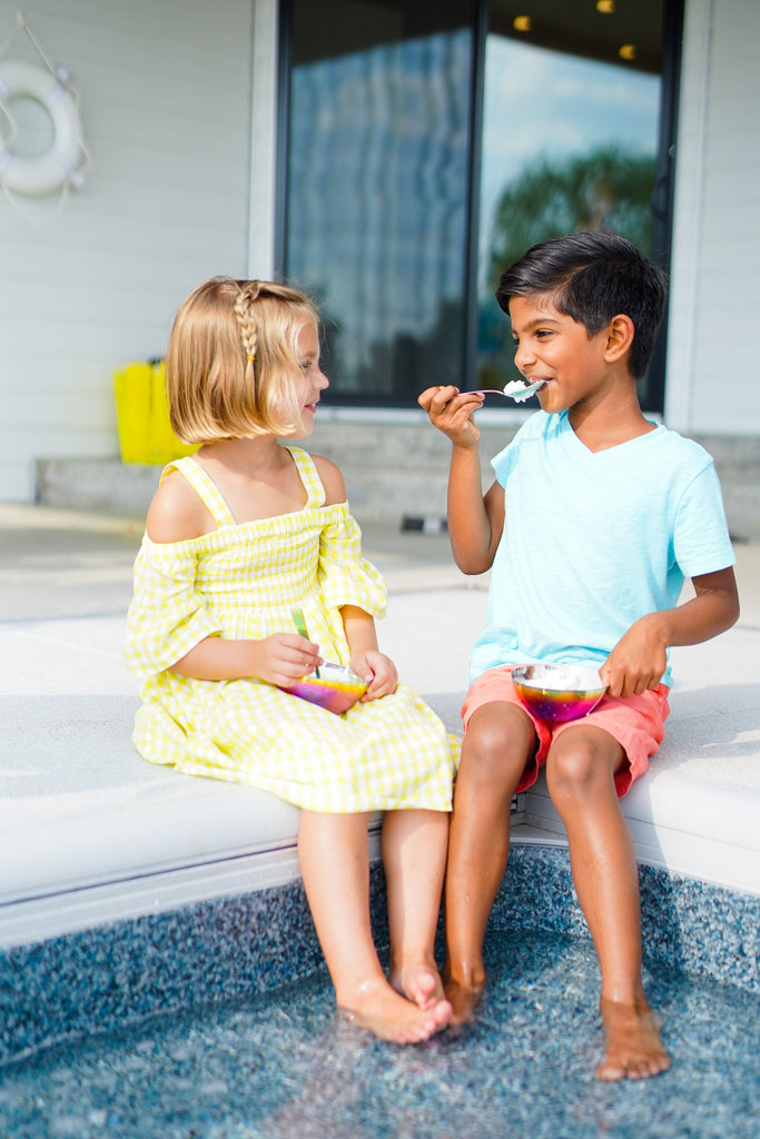 Two children using rainbow stainless steel bowls and spoons, non-toxic, plastic-free, 100% metal, no chipping or peeling