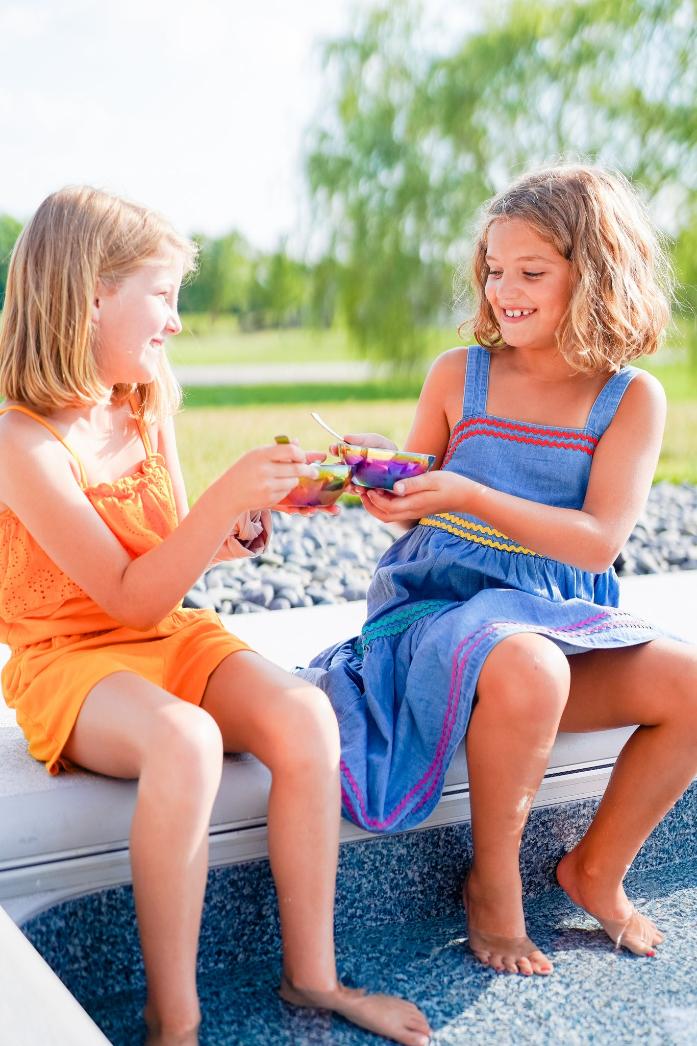 Two children using rainbow and blue stainless steel bowls and spoons non-toxic, plastic-free, 100% metal, no chipping or peeling