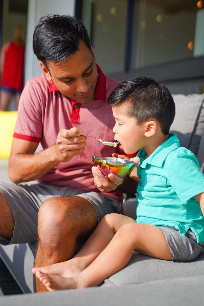 Father feeding son with rainbow stainless steel bowl and spoon, non-toxic, plastic-free, 100% metal, no chipping or peeling