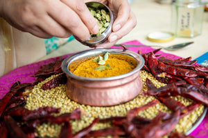 curry powder in bowl surrounded by dried chillies.