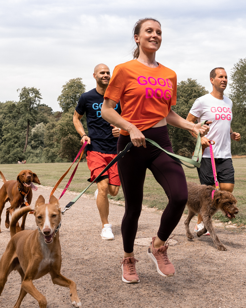 Orangenes Shirt mit Good Dog in neon orange fotografiert beim joggen mit Hund.