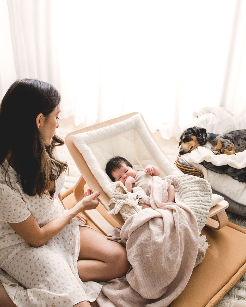 Mother with her newborn baby in a Charlie Crane Levo Rocker on a Tami Mat with a dog sleeping in the background