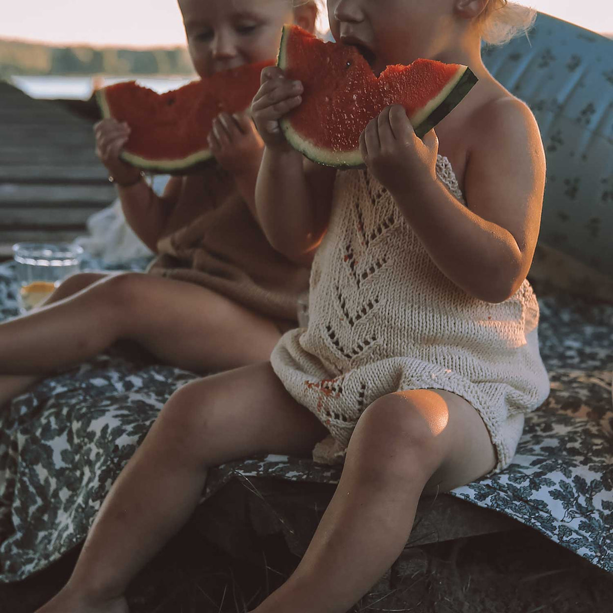 Perfect picnic blanket - two kids enjoying a slice of watermelon on a Garbo&Friends premium children's blanket in Woodland pattern