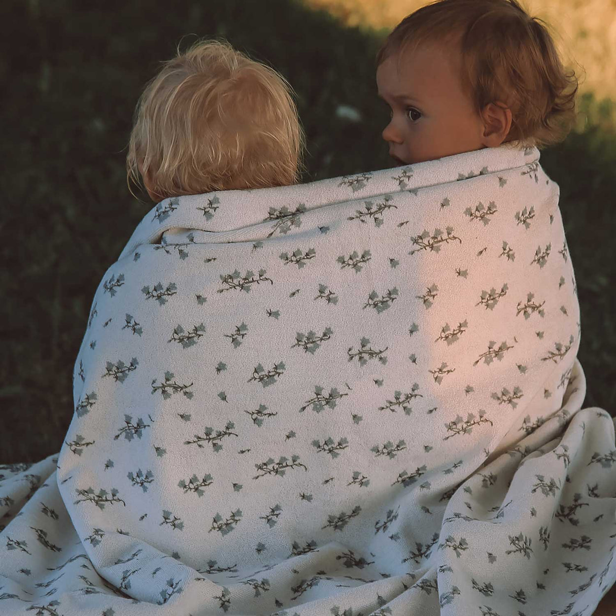 Little friends snuggled up in a Garbo&Friends gender-neutral floral pattern towel