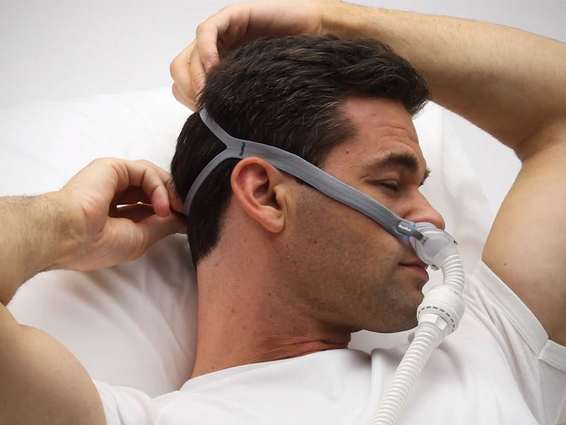 Man adjusting the straps of ResMed AirFit P10 For AirMini nasal pillows CPAP mask