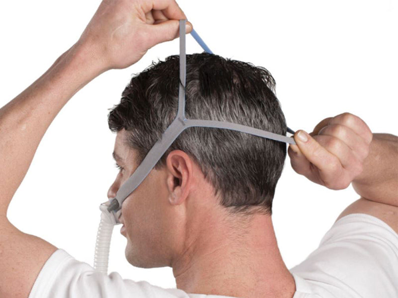 Man adjusting the straps of the ResMed AirFit™ P10 Nasal Pillows CPAP Mask