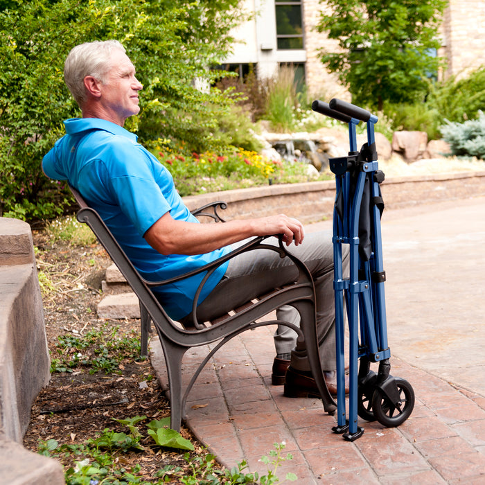 Man sitting next to a folded Stander EZ Fold-N-Go Walker Cobalt Blue
