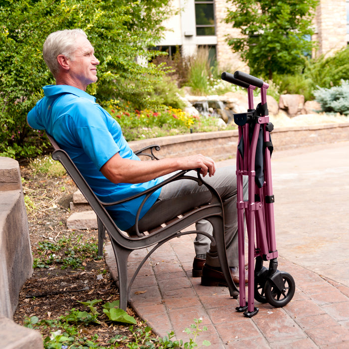 Man sitting next to a folded Stander EZ Fold-N-Go Walker Regal Rose