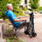 Man sitting next to a folded Stander EZ Fold-N-Go Walker Walnut Black