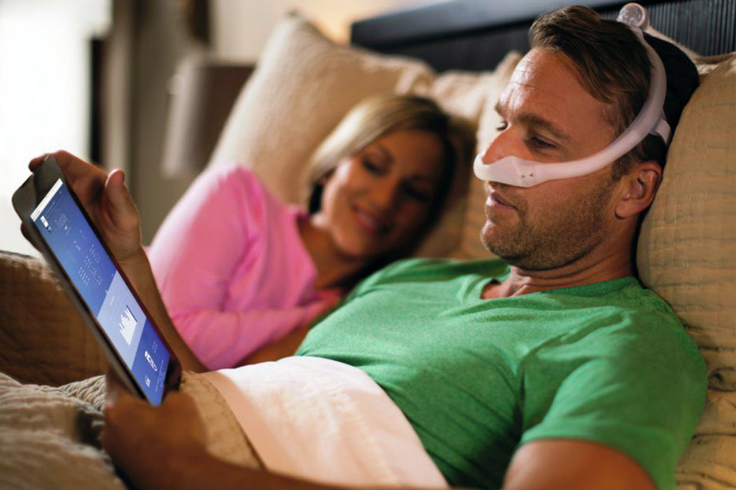 Man wearing the Philips Respironics DreamWear Nasal CPAP mask while reading