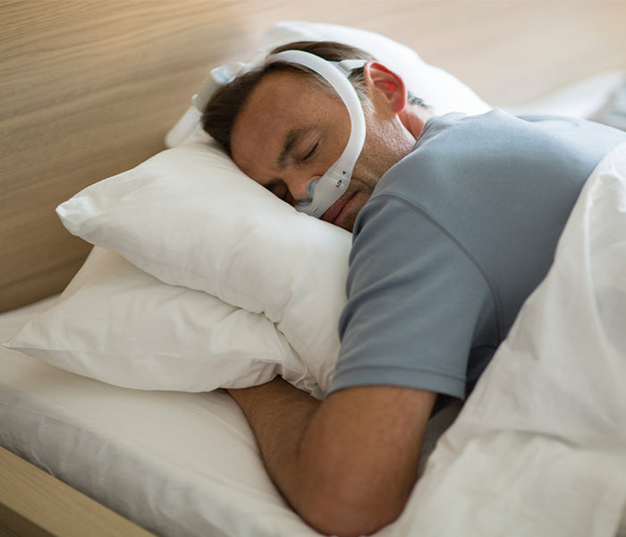 Philips Respironics DreamWear Gel Pillows CPAP mask worn by a sleeping man