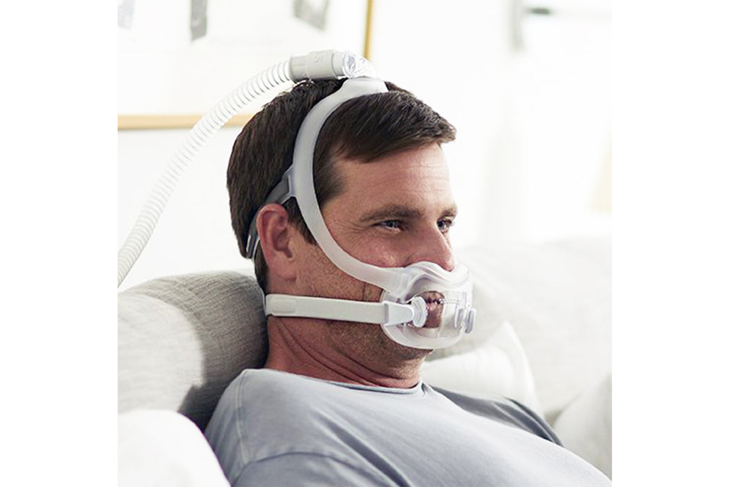 Philips Respironics DreamWear Full Face CPAP mask worn by man sitting down
