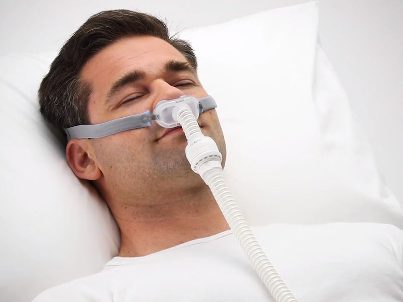 Sleeping man wearing the ResMed AirFit P10 For AirMini nasal pillows CPAP mask with headgear