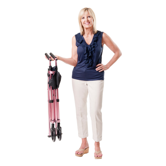 Woman holding a folded Stander EZ Fold-N-Go Walker Regal Rose
