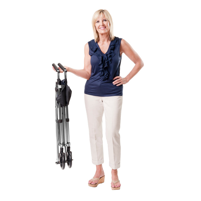 Woman holding a folded Stander EZ Fold-N-Go Walker Walnut Black