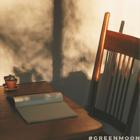 A journal sits on a table in front of an empty chair