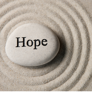 Grey oval stone engrained with the word hope is sitting in the sand. There are four circles drawn in the sand around the rock.