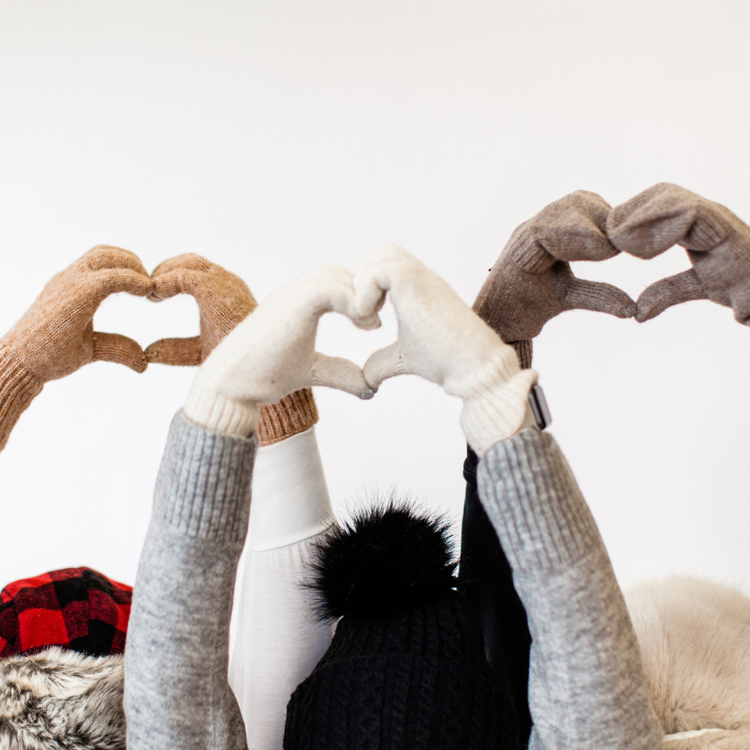 an image of three sets of arms raised in the air and each set of hands is forming the shape of a heart. The people are wearing gloves and mittens and you can see the tops of their hats and the hands to the elbows.