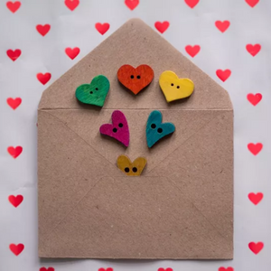 An envelope made of manila paper is open and there are six small hearts (green, red, pink, turquoise and two yellow). The envelope is laying on paper that is covered in small red hearts.