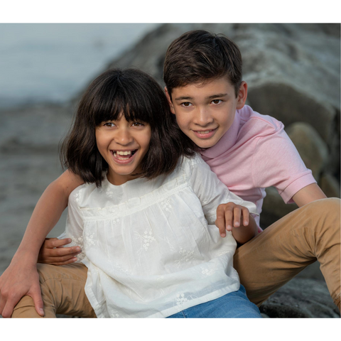 two siblings sitting together at the beach, the kids are facing the camera and smiling