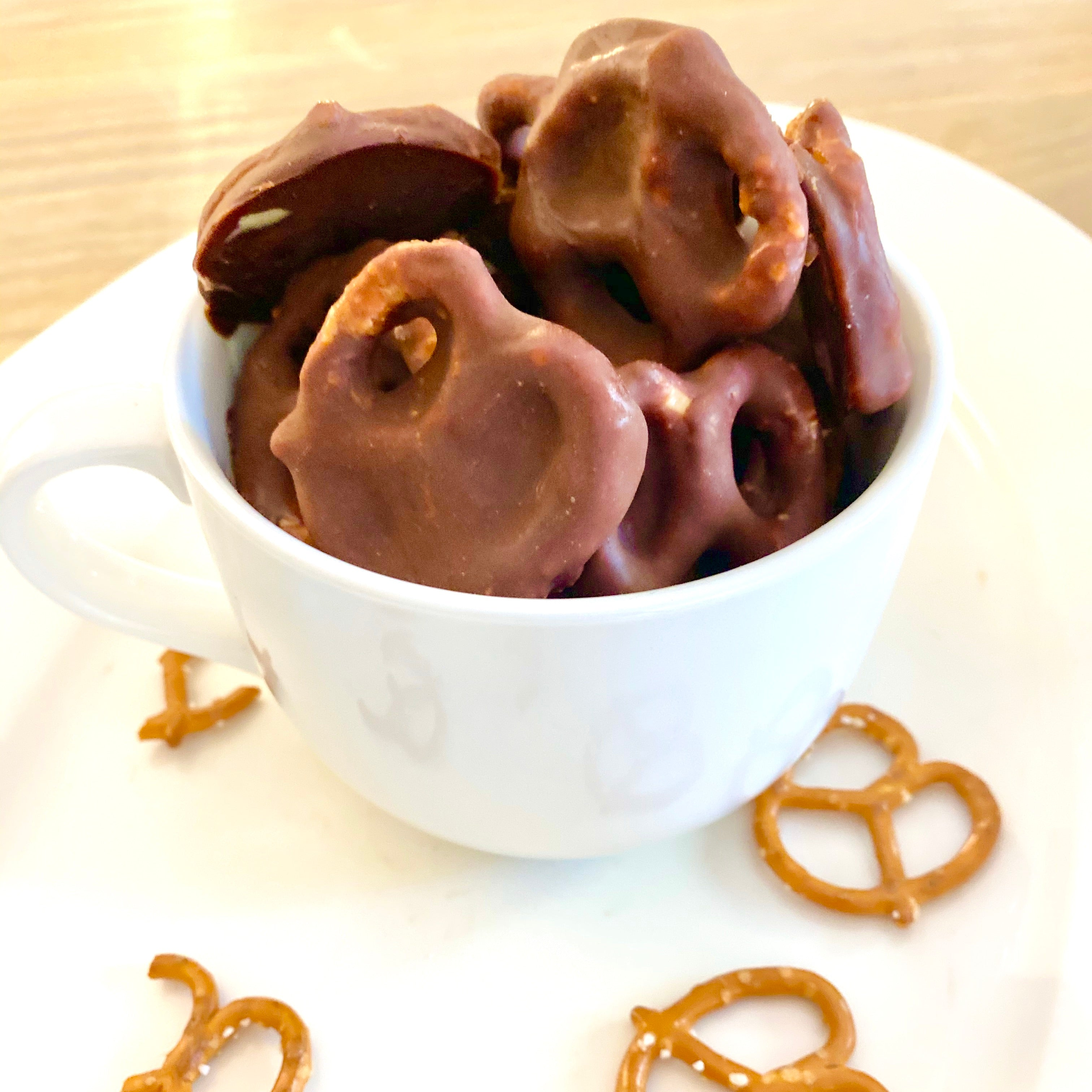 Pretzels covered in Natural Peanut Butter and chocolate, in a mug.