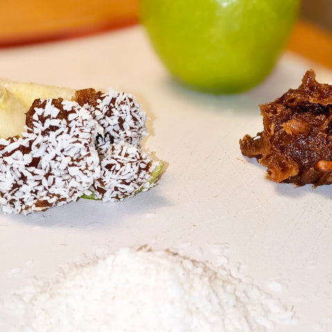 Sliced apple with natural peanut butter caramel date sauce spread, sprinkled with coconut shavings on top.