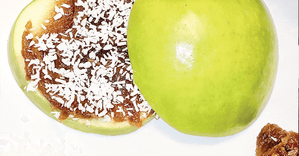 Sliced apple with a date sauce spread on top, sprinkled with coconut bits