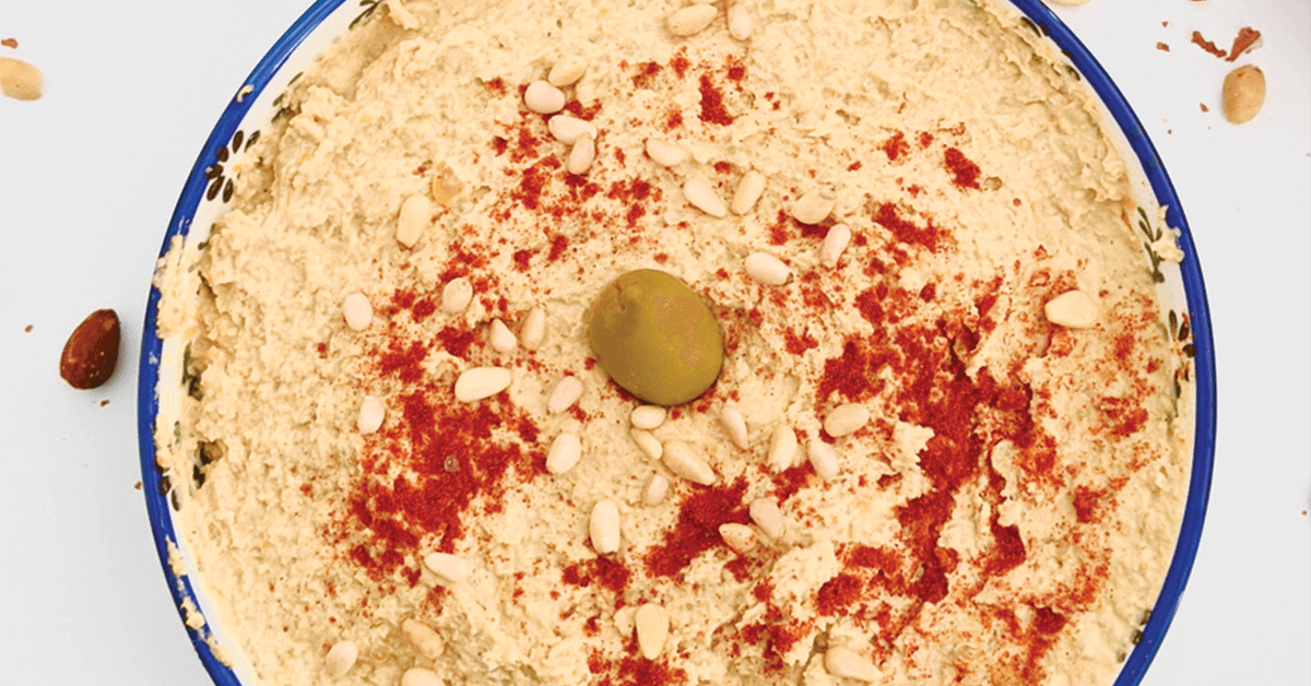Close up of bowl filled with hummus, topped with an olive and sprinkled with paprika