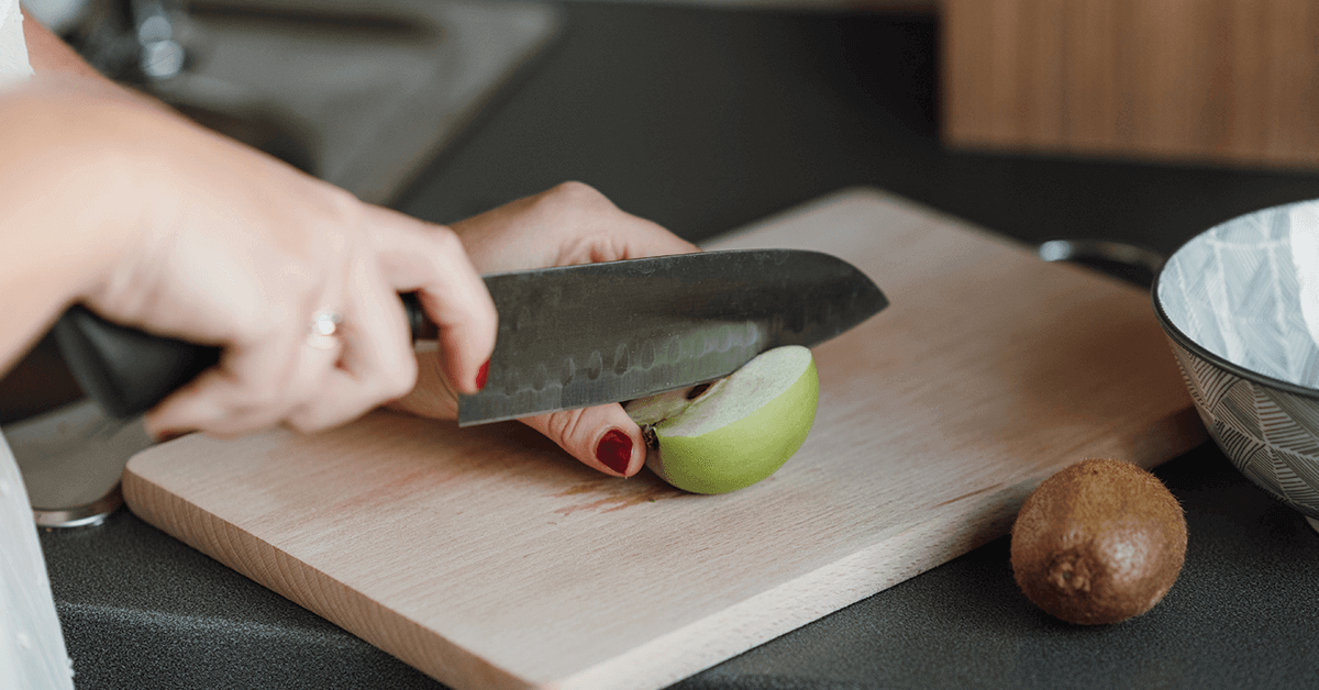 Green apple on cutting board being sliced with knife