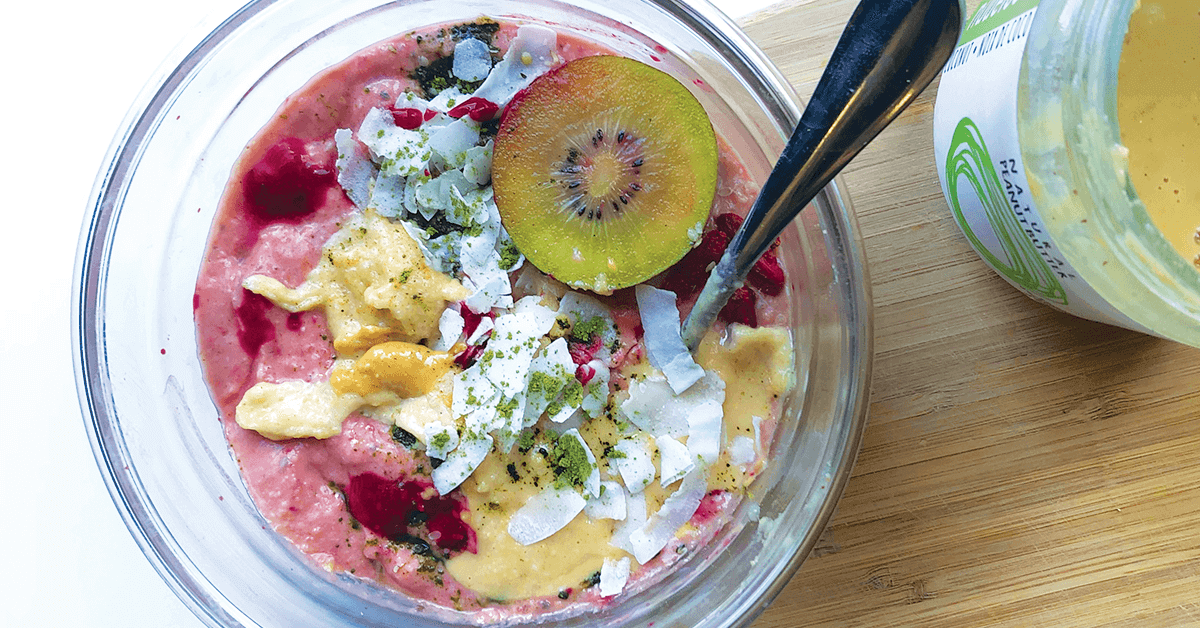 Pink smoothie bowl topped with kiwi, coconut, matcha, and peanut butter