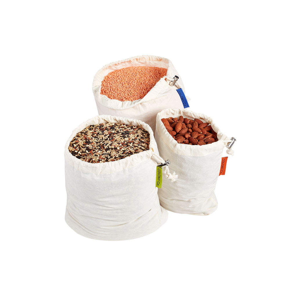 Three different sized cotton bags filled with lentils, rice, and almonds.