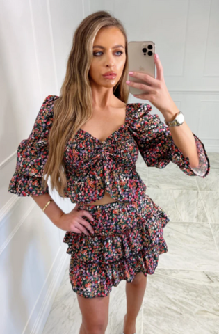 Model wearing Glamify Aurora two piece co-ord with skirt and holding an iphone