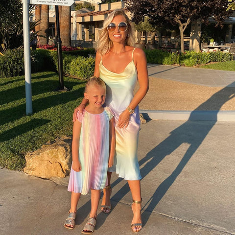 Billie Faiers and daughter Nelly stood outside in the sunshine wearing matching rainbow dresses